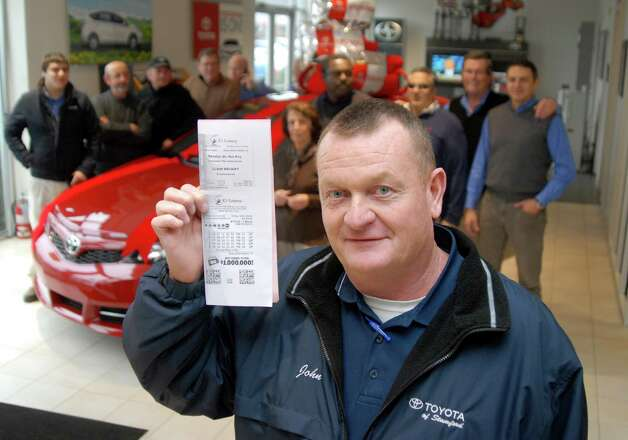 John Linn, general manager of Toyota/Scion of Stamford holds a copy of winning Powerball ticket on Friday November 30, 2012, 23 members of Toyota of Stamford's sales and service staff are going to split a $1 million prize for matching five of the winning Powerball numbers in Wednesday's record jackpot. Each will receive about $30,000 after taxes. Photo: Dru Nadler / Stamford Advocate Freelance