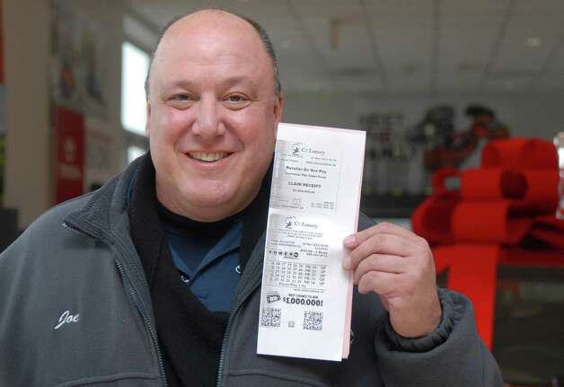 Joe Carbonell of Toyota/Scion of Stamford holds a copy of winning Powerball ticket on Friday November 30, 2012 that he'll share with 23 members of Toyota of Stamford's sales and service staff who are going to split a $1 million prize for matching five of the winning Powerball numbers in Wednesday's record jackpot. Each will receive about $30,000 after taxes. Carbonell was the one who bought the quick pick ticket. Photo: Dru Nadler / Stamford Advocate Freelance