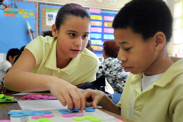 Aliyah Martinez and Brandon Young, 5th graders at Black Rock School, in Bridgeport, Conn. works together on a math exercise Nov. 30th, 2012. Photo: Ned Gerard / Connecticut Post