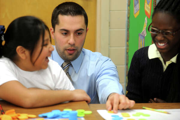 Math coach John Tavella works with 5th graders Kimberly Zentle, left, and Kadarah Elliston during a math class at Black Rock School, in Bridgeport, Conn. Nov. 30th, 2012.
