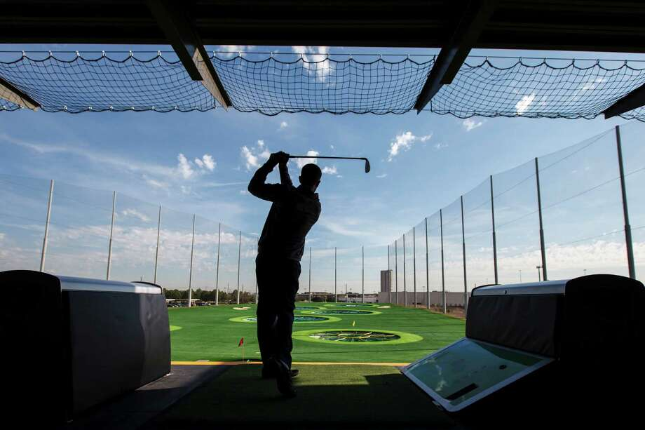 Jason Fuller hits a golf ball at TopGolf, a 64,000-square-foot golf entertainment complex, Monday, Nov. 19, 2012, in Houston.  TopGolf features 102 golf bays on 3 floors and a rooftop terrace along with several bars.  ( Michael Paulsen / Houston Chronicle ) Photo: Michael Paulsen, Staff / © 2012 Houston Chronicle
