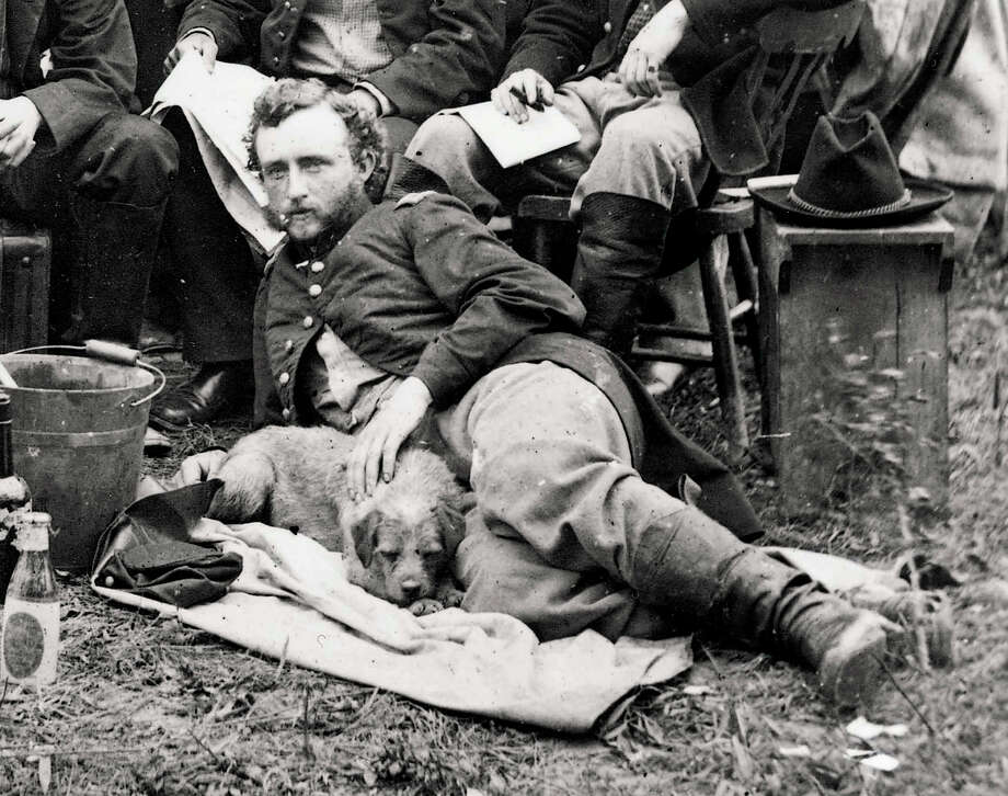 FILE - This May 20, 1862, file photograph from the Library of Congress shows a young Lt. George A. Custer reclining with a dog for a portrait with fellow staff members of General Fitz-John Porter, during the Civil War in Virginia. Years before leading his vastly outnumbered troops to their doom at Little Bighorn, a young George Armstrong Custer was described as accurate in math. This is just one tidbit gleaned from more than 115,000 U.S. Military Academy application documents being posted online for the first time by Ancestry.com. (AP Photo/Library of Congress, James F. Gibson, File) Photo: JAMES F. GIBSON, HO / Library of Congress