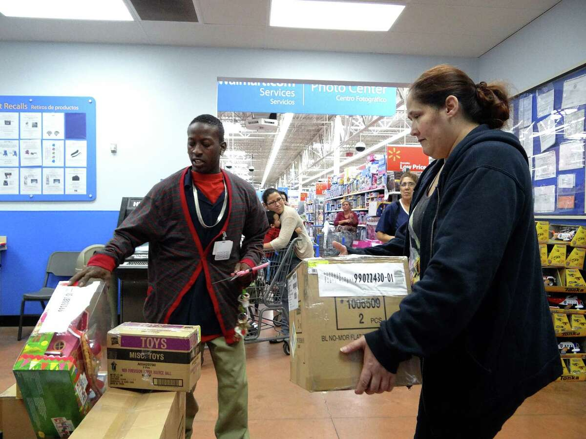 Walter Carmichael, left, assists customer Valerie Bigelow with her layaway items at the West Military Drive WalMart on Friday, Nov. 30, 2012.