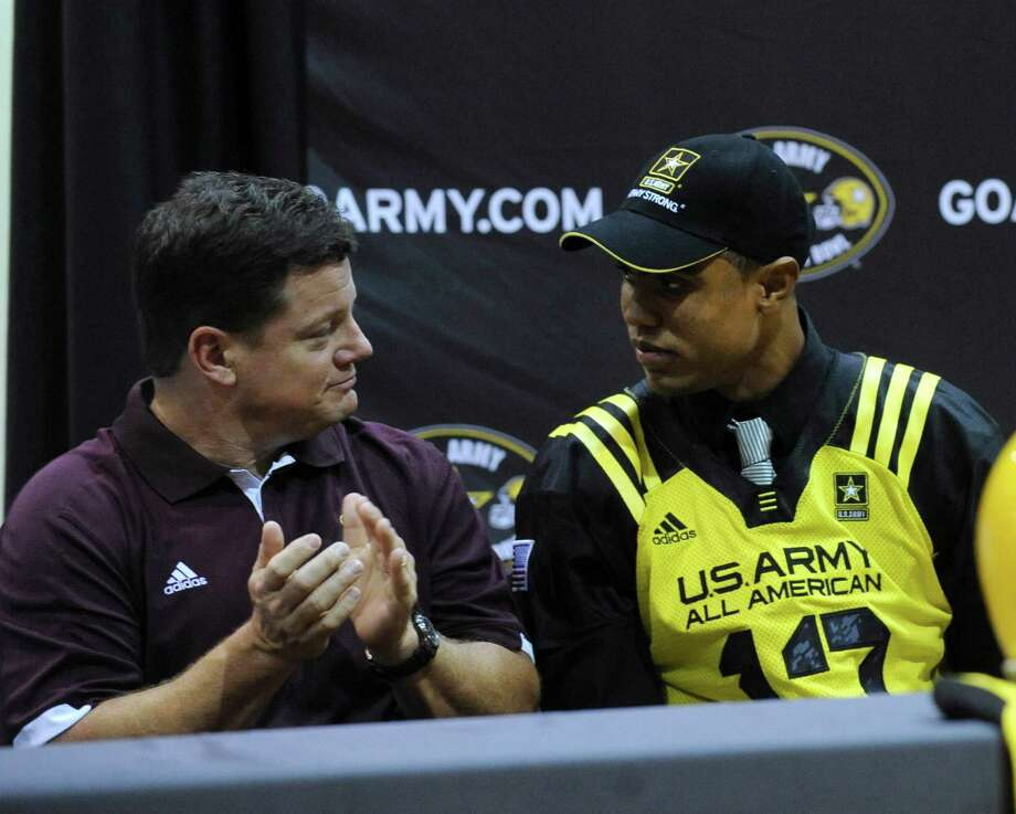 Corey Robinson, right, is applauded by his coach, Bryan Marmion of San Antonio Christian High School, during a ceremony to announce his selection to the U.S. Army All-American Bowl on Friday, Nov. 30, 2012. Robinson is the son of NBA legend David Robinson. He has committed to playing college football at Notre Dame. Photo: Billy Calzada, Express-News / SAN ANTONIO EXPRESS-NEWS