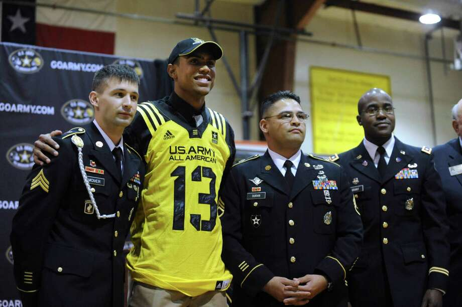 Corey Robinson, second from left, poses with Sgt. Brent McIver, left, Staff Sgt. Samuel Duran and Lt. Col. David A. Grant, right, after Robinson's selection to the U.S. Army All-American Bowl at San Antonio Christian High School on Friday, Nov. 30, 2012. Robinson leads the area with 1,414 receiving yards and 20 touchdowns in 2012. Photo: Billy Calzada, Express-News / SAN ANTONIO EXPRESS-NEWS