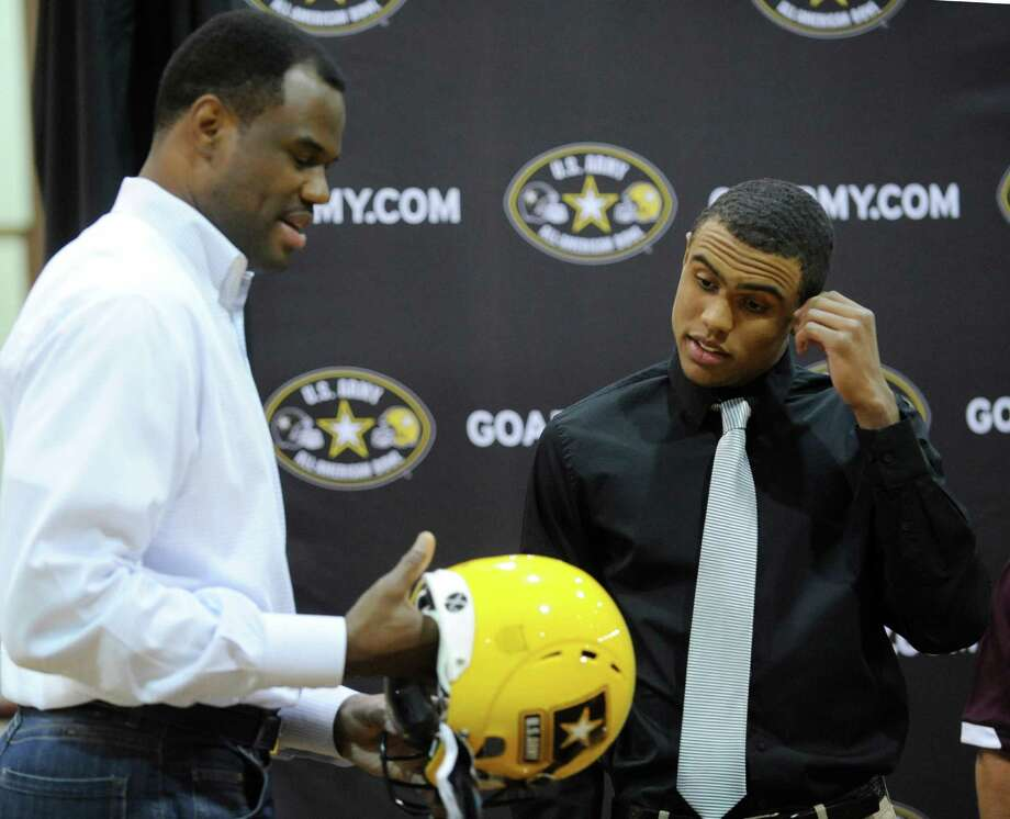 Corey Robinson, right, who has been selected to play in the U.S. Army All-American Bowl, and his father, NBA legend David Robinson, inspect a bowl helmet during a ceremony at San Antonio Christian High School on Friday, Nov. 30, 2012. Corey Robinson has committed to playing college football at Notre Dame. Photo: Billy Calzada, Express-News / SAN ANTONIO EXPRESS-NEWS