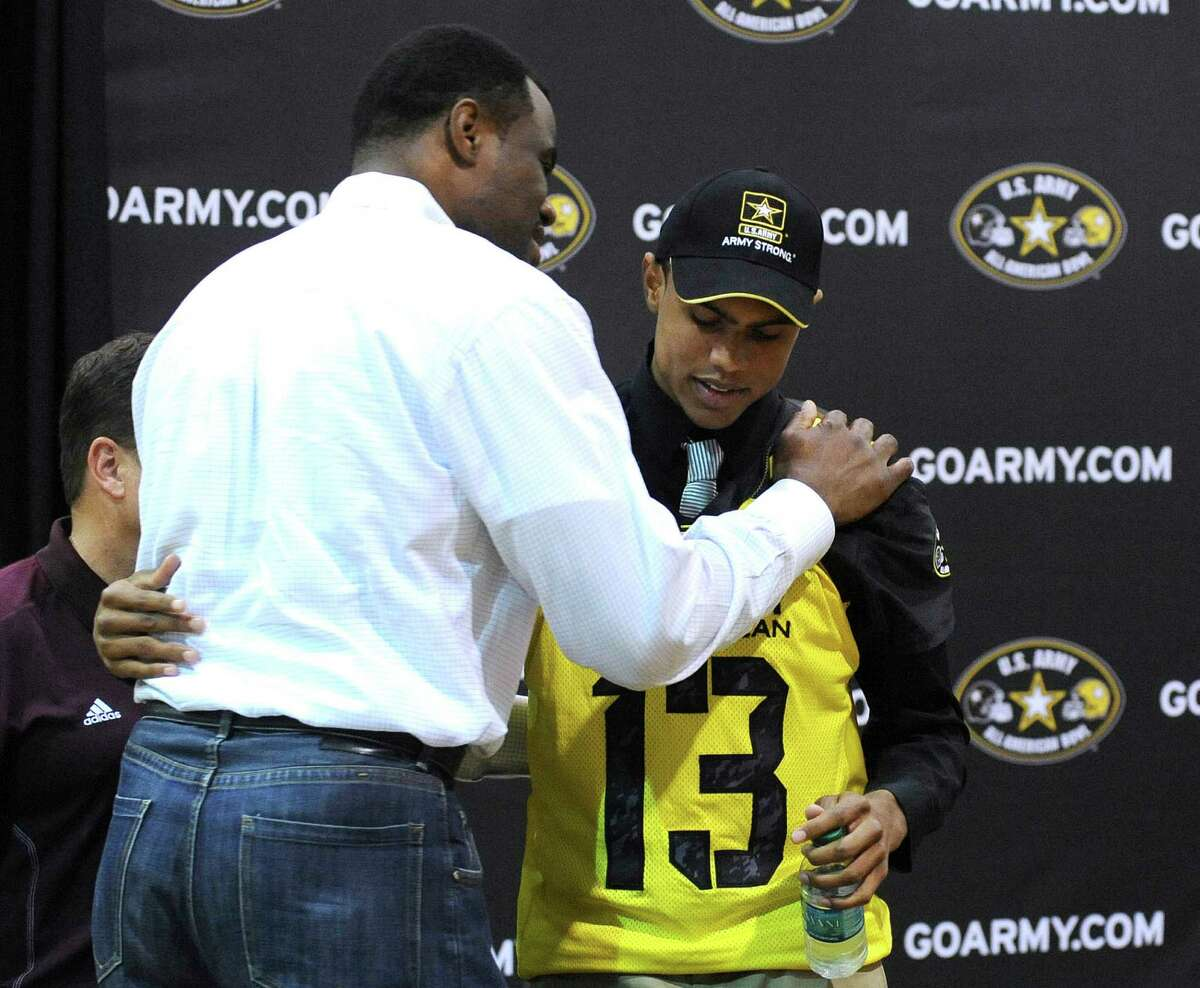 Corey Robinson, a receiver for San Antonio Christian High School, is embraced by his father, basketball legend David Robinson, after Corey was selected to play in the U.S. Army All-American Bowl during a ceremony at San Antonio Christian High School on Friday, Nov. 30, 2012.