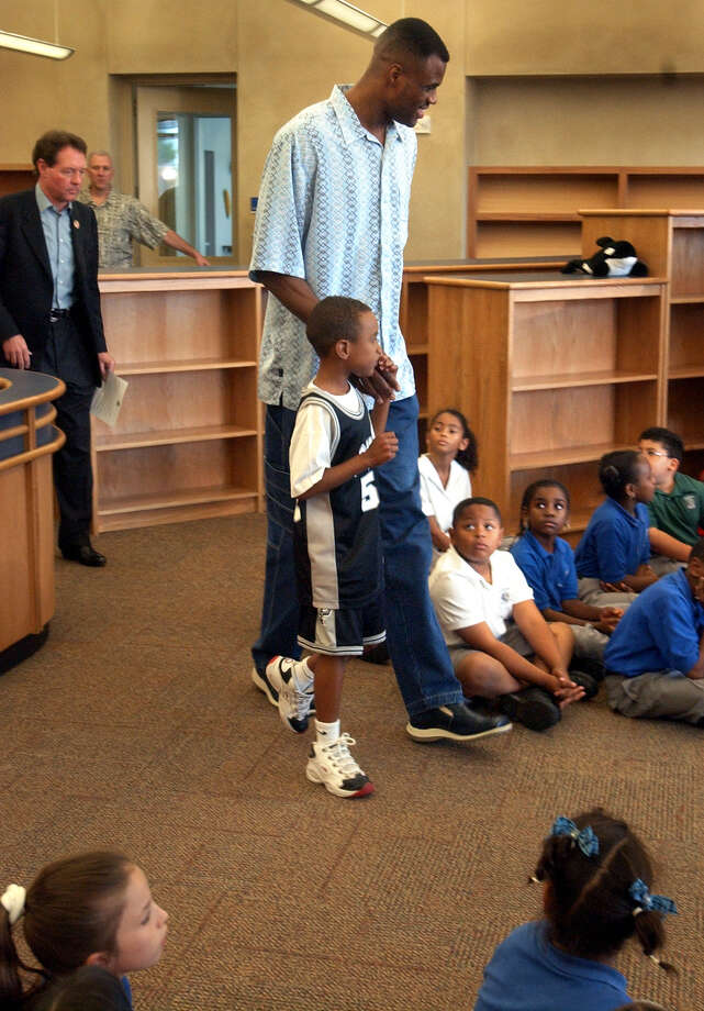 San Antonio Spurs David Robinson walks into the Library at the Carver Academy with his son Corey to announce that he will retire after the next NBA season, Friday, May, 24, 2002. photo bob Owen Photo: BOB OWEN, Express-News / SAN ANTONIO EXPRESS-NEWS
