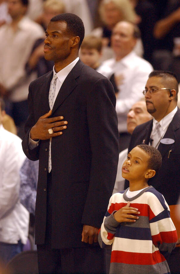 Former San Antonio Spurs David Robinson and his son, Corey, 8, salute during the Natnional Athem prior to the start of the Spurs Jazz game at the Alamodome on Monday, Nov. 10, 2003. (JERRY LARA STAFF ) Photo: JERRY LARA, Express-News / SAN ANTONIO EXPRESS-NEWS