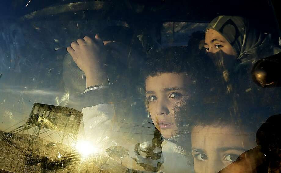 Syrian children peer out as their car crosses into Lebanon. Fighting killed at least 56 on Friday. Photo: Hassan Ammar, Associated Press
