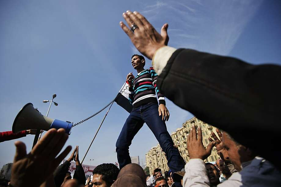"An Egyptian man delivers a speech as protesters gather in Cairo's landmark Tahrir square on November 30, 2012, to protest against a decree by President Mohamed Morsi granting himself broad powers that shield his decisions from judicial review. A coalition of leading dissidents has called for protest rallies, including in Cairo's Tahrir Square where three days ago tens of thousands vented their anger at Morsi's decree, denouncing him as a ""dictator"" in the mould of toppled president Hosni Mubarak. Photo: Gianluigi Guercia, AFP/Getty Images"