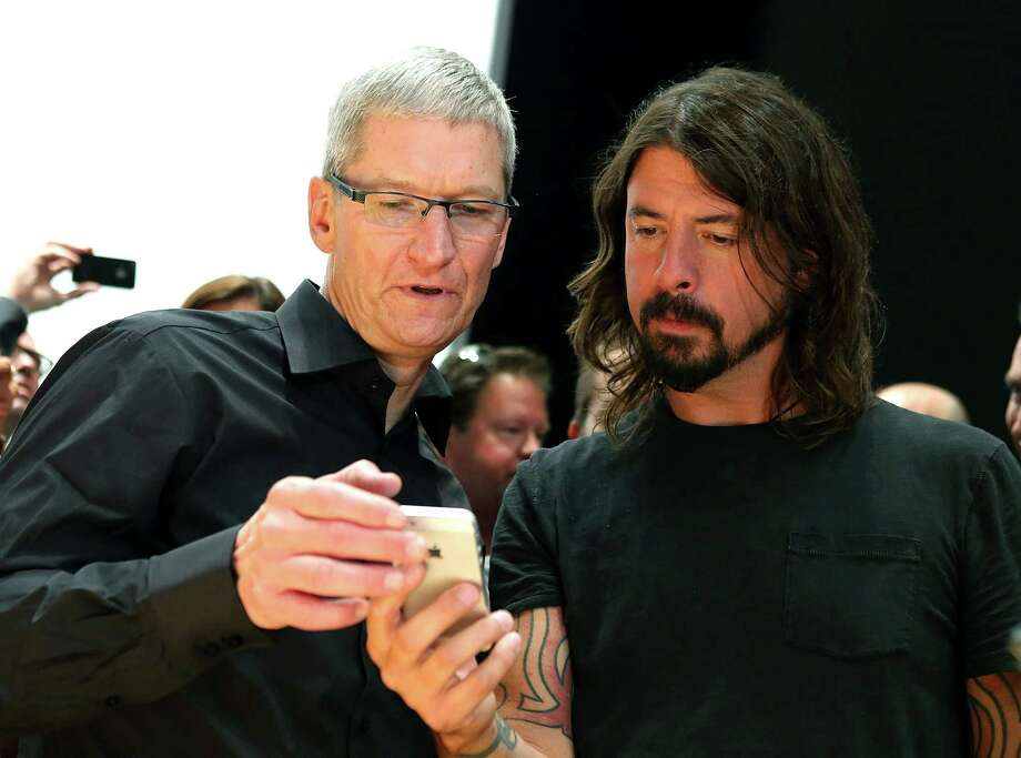 Apple CEO Tim Cook (left) and Dave Grohl of the Foo Fighters look at the new iPhone 5 during an Apple special event at the Yerba Buena Center for the Arts on September 12, 2012 in San Francisco, California. Apple announced the iPhone 5, the latest version of the popular smart phone. Photo: Justin Sullivan, Getty Images / 2012 Getty Images