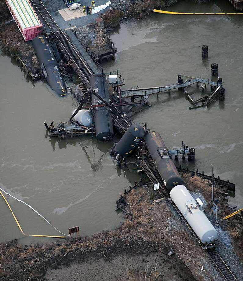 Several cars lay in the water after a freight train derailed in Paulsboro, N.J., Friday, Nov. 30, 2012. People in three southern New Jersey towns were told Friday to stay inside after the freight train derailed and several tanker cars carrying hazardous materials toppled from a bridge and into a creek. Photo: Cliff Owen, Associated Press