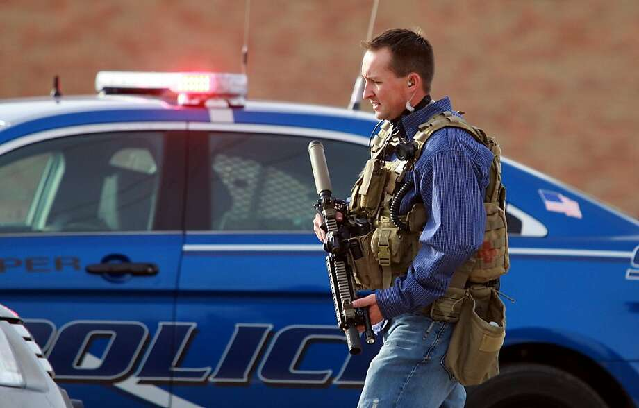 A sheriff's deputy in Natrona County, Wyo., helps secure the Casper College campus, where two people were killed. Photo: Alan Rogers, Associated Press