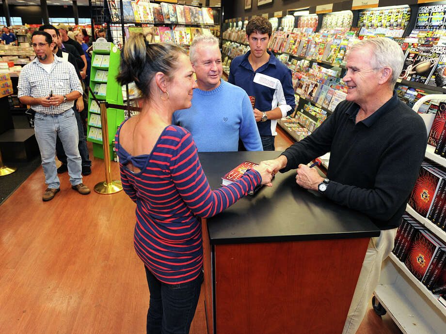 Patricia McKinley shakes Oliver North's hand after having the retired Marine sign her copy of his new book at Books-A-Million in Beaumont Friday. The Lieutenant Colonel describes his experiences in global situations and military action. Harry McKinley looks on. Photo taken Friday, November 29, 2012 Guiseppe Barranco/The Enterprise Photo: Guiseppe Barranco, STAFF PHOTOGRAPHER / The Beaumont Enterprise