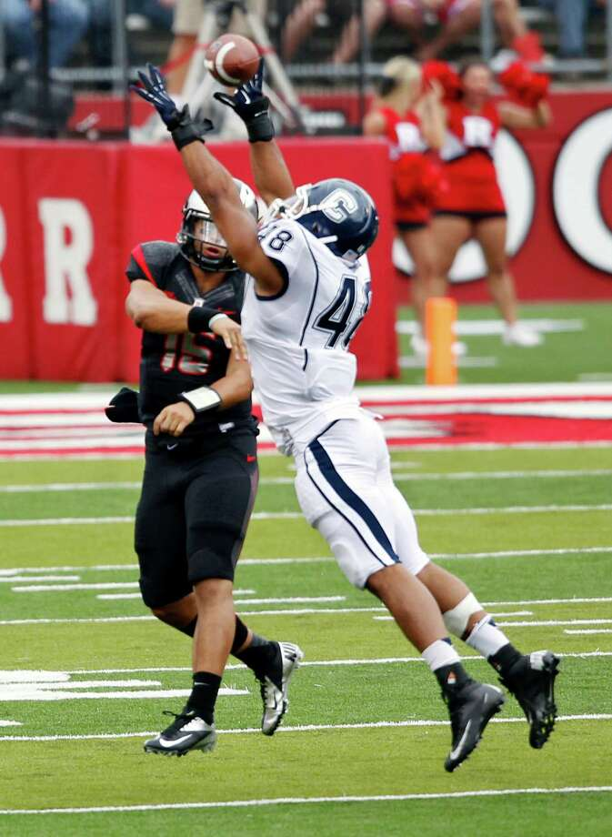 Connecticut defensive end Trevardo Williams (48) tries to block a pass by Rutgers quarterback Gary Nova during the first half of an NCAA college football game in Piscataway, N.J., Saturday, Oct. 6, 2012. (AP Photo/Mel Evans) Photo: Mel Evans, Associated Press / AP