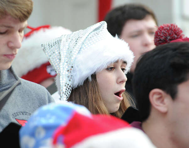 "At center, Tory Hoffmeister, 17, of the Greenwich High School Chamber Singers, sings ""We Wish You a Merry Christmas,"" along with fellow chamber singers during the Department of Parks and Recreation annual tree-lighting ceremony at Greenwich Town Hall, Friday afternoon, Nov. 30, 2012. Photo: Bob Luckey / Greenwich Time"