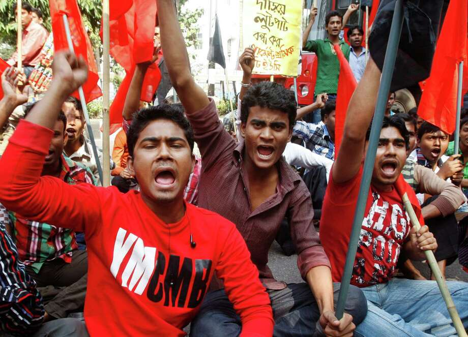 "Bangladeshi garment workers shout slogans as they participate in a protest to mourn the death of the victims of a fire in a garment factory in Dhaka, Bangladesh, Friday, Nov. 30, 2012. Hundreds of garment workers protested Friday outside the Bangladeshi factory where 112 people were killed by the fire, demanding compensation for their lost salaries. The placard behind reads: ""Stop looting from the garment sector."" (AP Photo/Pavel Rahman) Photo: Pavel Rahman"
