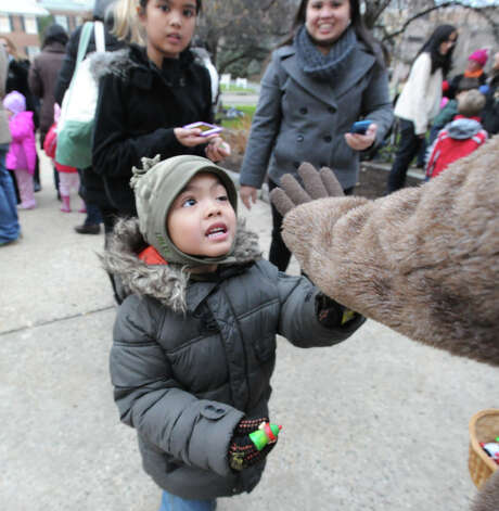 Troy Rumbaoa, 4, of Greenwich, touches the hand of Rudolph the Red-Nosed Reindeer during the Department of Parks and Recreation annual tree-lighting ceremony at Greenwich Town Hall, Friday afternoon, Nov. 30, 2012. Photo: Bob Luckey / Greenwich Time