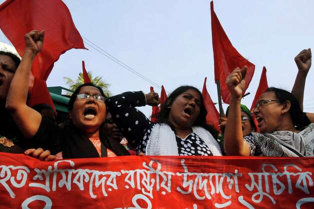 "Bangladeshi garment workers shout slogans as they participate in a protest to mourn the death of the victims of a fire in a garment factory in Dhaka, Bangladesh, Friday, Nov. 30, 2012. Hundreds of garment workers protested Friday outside the Bangladeshi factory where 112 people were killed by the fire, demanding compensation for their lost salaries. The banner reads: ""We demand financial help for the workers."" (AP Photo/Pavel Rahman) Photo: Pavel Rahman"