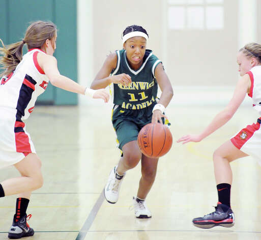 At center, Kennedy Woods # 11 of Greenwich Academy, splits a pair of Kingswood-Oxford School players while dribbling upcourt during the O'Neil S. Medley Memorial Basketball Tournament at Greenwich Academy, Friday night, Nov. 30, 2012. Kingswood-Oxford defeated Greenwich Academy, 47-33. Photo: Bob Luckey / Greenwich Time