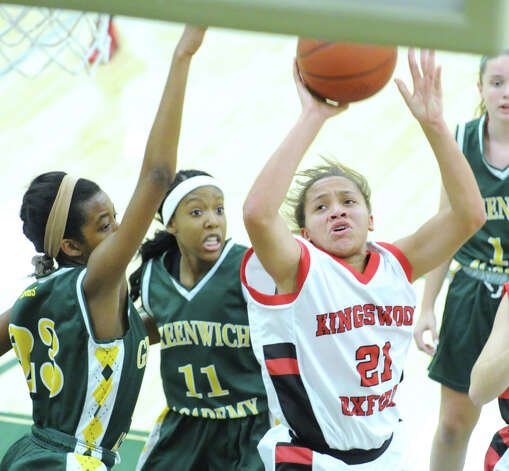 At right, Kingswood-Oxford School 's Jeanna Willis # 21 scores a basket getting past Kennedy Woods # 11 and Jubille Johnson # 23, both of Greenwich Academy, during the O'Neil S. Medley Memorial Basketball Tournament at Greenwich Academy, Friday night, Nov. 30, 2012. Kingswood-Oxford defeated Greenwich Academy, 47-33. Photo: Bob Luckey / Greenwich Time