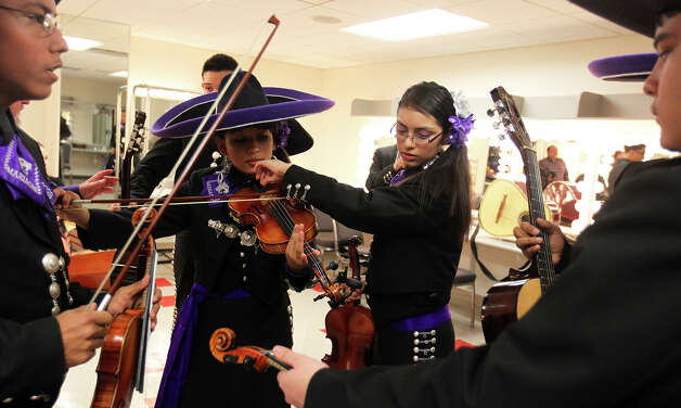 Justine Williams, left, gets help tuning her violin from Elizabeth Guzman as Mariachi Pantera from Jefferson Davis High School in Houston prepares for the Group Competition during the 18th annual Mariachi Vargas Extravaganza at  Lila Cockrell Theatre, Friday, November 30, 2012. Photo: JENNIFER WHITNEY / © Jennifer Whitney