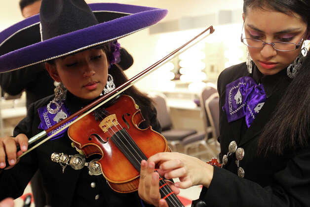 Justine Williams, left, gets help tuning her violin from Elizabeth Guzman as Mariachi Pantera from Jefferson Davis High School in Houston prepares for the Group Competition during the 18th annual Mariachi Vargas Extravaganza at  Lila Cockrell Theatre, Friday, November 30, 2012. (JENNIFER WHITNEY) Photo: JENNIFER WHITNEY, For The Express-News / © Jennifer Whitney