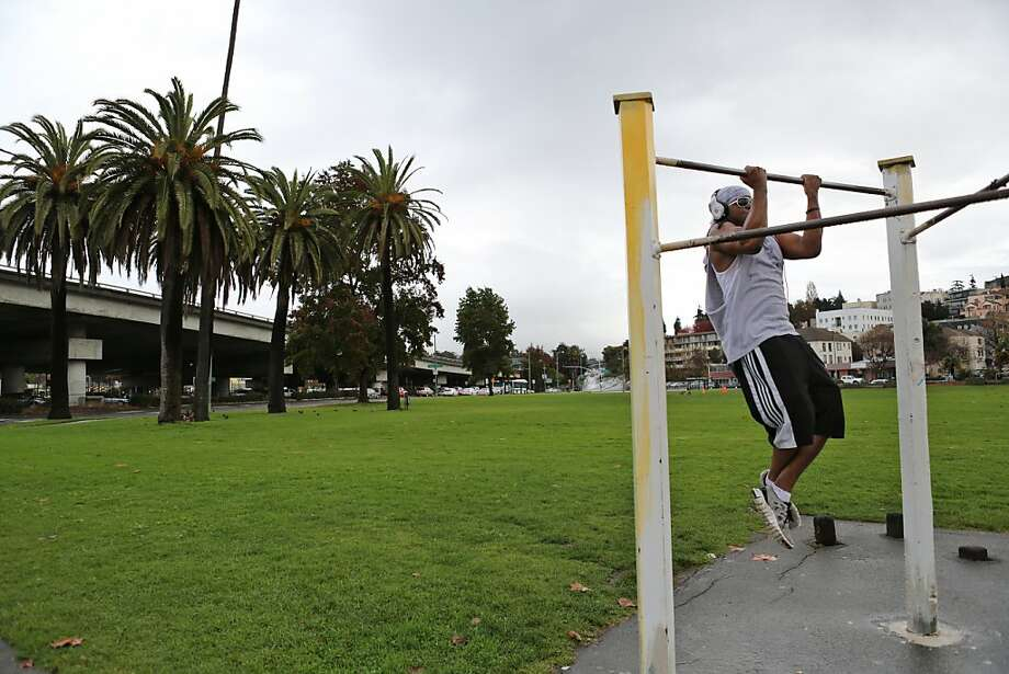 Anthony Jackson exercises in the park; a dog park is proposed on the far side (background). Photo: Rashad Sisemore, The Chronicle