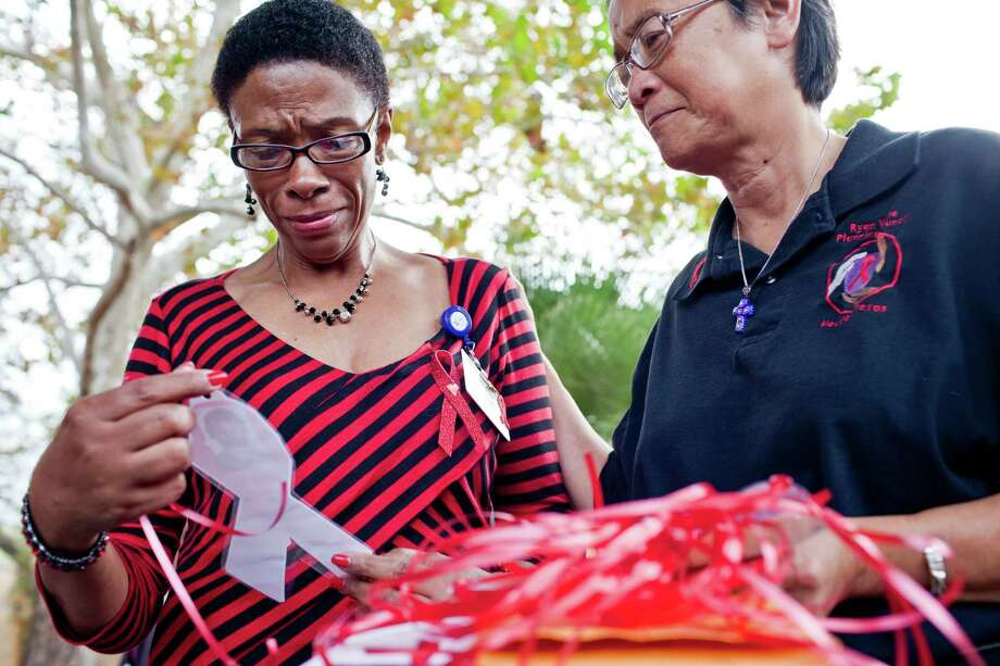 "Charlotte Harris, until being handed a memorial ornament Friday by Georgette Monaghan at the Thomas Street Health Center, did not know that Eulalia ""Lady"" Seymore, a friend and fellow AIDS patient, had died. Photo: Eric Kayne / © 2012 Eric Kayne"