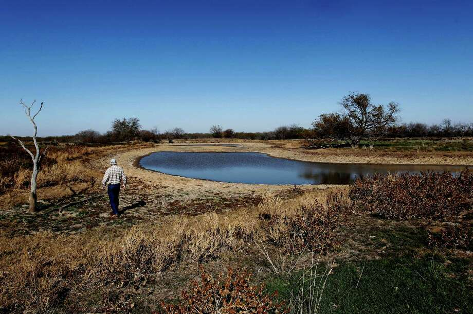 In this Thursday, Nov. 29, 2012 photo, Darrell Francis walks on what was the bottom of a pond on his ranch near Perrin, Texas. A dry winter that is on track to making the record books has sent portions of Texas, including Houston and Fort Worth, back into severe drought, raising concerns about wildfires and the health of wheat crops and tree farms, climatologists said. (AP Photo/The Fort Worth Star-Telegram, Ron Jenkins)  MAGS OUT; (FORT WORTH WEEKLY, 360 WEST); INTERNET OUT Photo: Ron Jenkins, MBI / The Fort Worth Star-Telegram