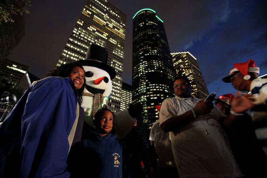 Penny Collier and son Brad Randell, 8, take a photo with an oversized snowman during the Mayor's 2012 Holiday Celebration and Tree Lighting at City Hall on Friday, Nov. 30, 2012, in Houston. Photo: Mayra Beltran, Houston Chronicle / © 2012 Houston Chronicle