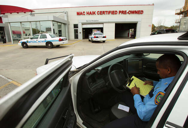 An officer sits in his car after a shooting occurred at a Katy Freeway used car dealership on Friday. A salesman wounded the sales manager with a pistol after a confrontation in the supervisor's office, police said. Photo: Cody Duty, Staff / © 2012 Houston Chronicle