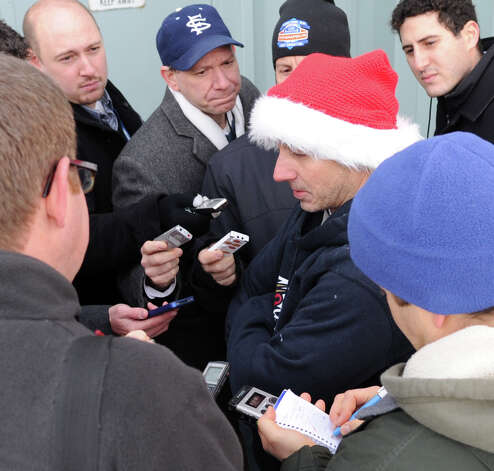 Reporters surround New York Yankees General Manager Brian Cashman after Cashman rappelled from the top of the Landmark Building in Stamford on Friday, November 30, 2012, as practice for Heights and Lights on Sunday, December 2, when Cashman, Bobby Valentine, and Stamford police officer Heather Franc will rappel at 5 p.m. Photo: Lindsay Niegelberg / Stamford Advocate
