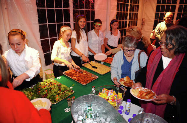 "Volunteers serve food to guests, during ""A Season We Share"" event at the annual Fairfield Christmas Tree Festival at Burr Homestead in Fairfield, Conn. on Friday November 30, 2012. Photo: Christian Abraham / Connecticut Post"