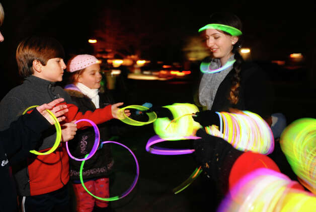 Lily Ling hands out glow necklaces to Sam Hawley, 12, and Amelia Garmett, 10, during the annual Christmas Tree Lighting on the Town Hall Green in Fairfield, Conn. on Friday November 30, 2012. Photo: Christian Abraham / Connecticut Post