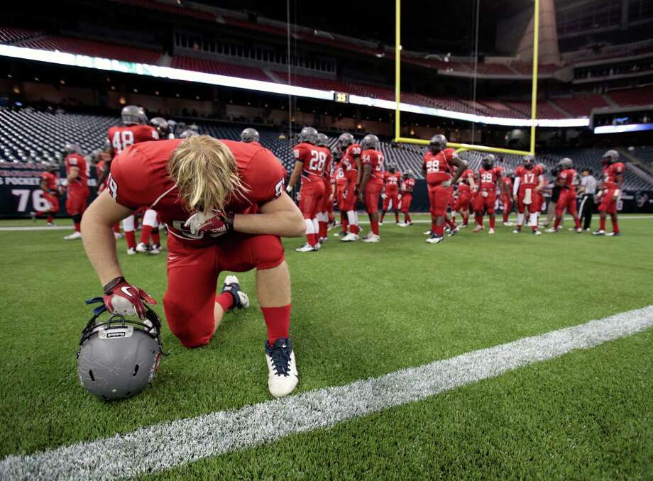 Dawson's Charles Watts prays before a Class 4A Division I high school football playoff game against Nederland. Photo: Eric Christian Smith, For The Chronicle