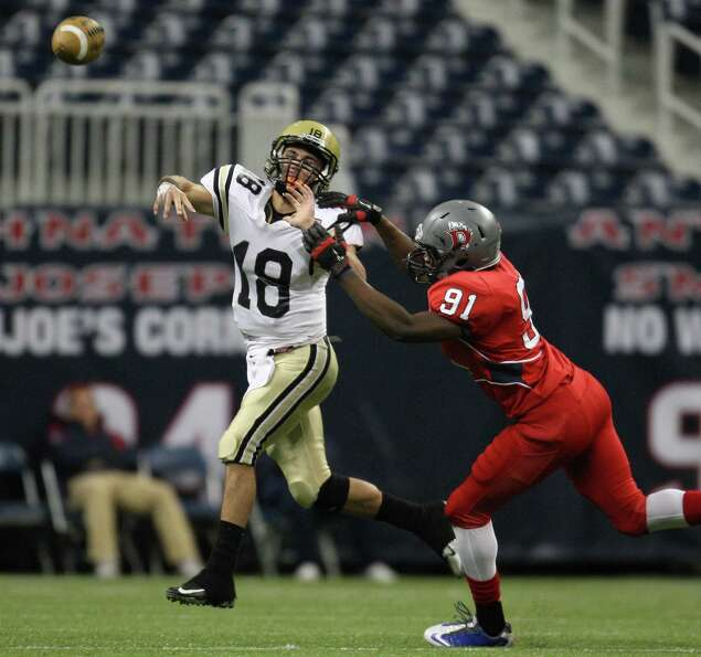 Nederland quarterback Carson Raines (18) passes the ball as Dawson's Brent Johnson defends.