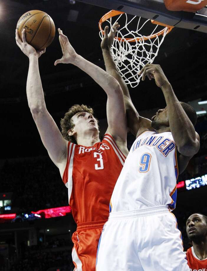 Omer Asik (3) shoots over Thunder forward Serge Ibaka. (AP Photo/Sue Ogrocki) (Associated Press)