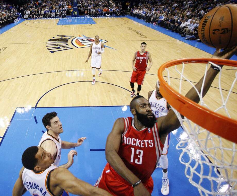 James Harden shoots in front of Thunder guard Thabo Sefolosha, left, and Nick Collison, second from left, in the second quarter. (AP Photo/Sue Ogrocki) (Associated Press)