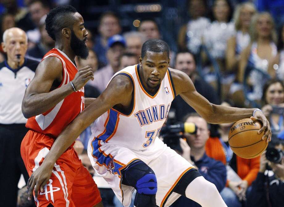 Kevin Durant (35) drives around James Harden, left, in the first quarter. (AP Photo/Sue Ogrocki) (Associated Press)