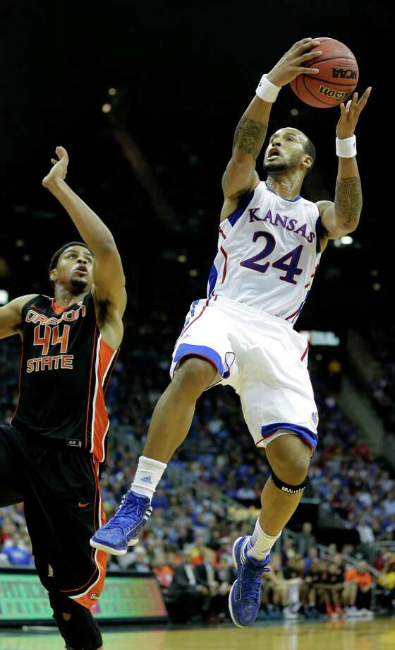 Kansas guard Travis Releford (24) gets past Oregon State forward Devon Collier (44) to put up a shot during the second half of an NCAA college basketball game on Friday, Nov. 30, 2012, in Kansas City, Mo. Kansas won the game 84-78. (AP Photo/Charlie Riedel) Photo: Charlie Riedel