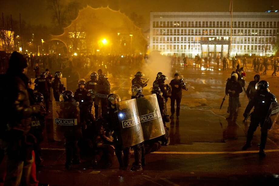 Riot police detain protesters outside the parliament building in Ljubljana, Slovenia, Friday, Nov. 30, 2012.  Thousands joined anti-government protests in Slovenia on Friday as tensions soared ahead of this weekend's presidential runoff in the small, economically struggling EU nation. Photo: Matej Leskovsek, Associated Press