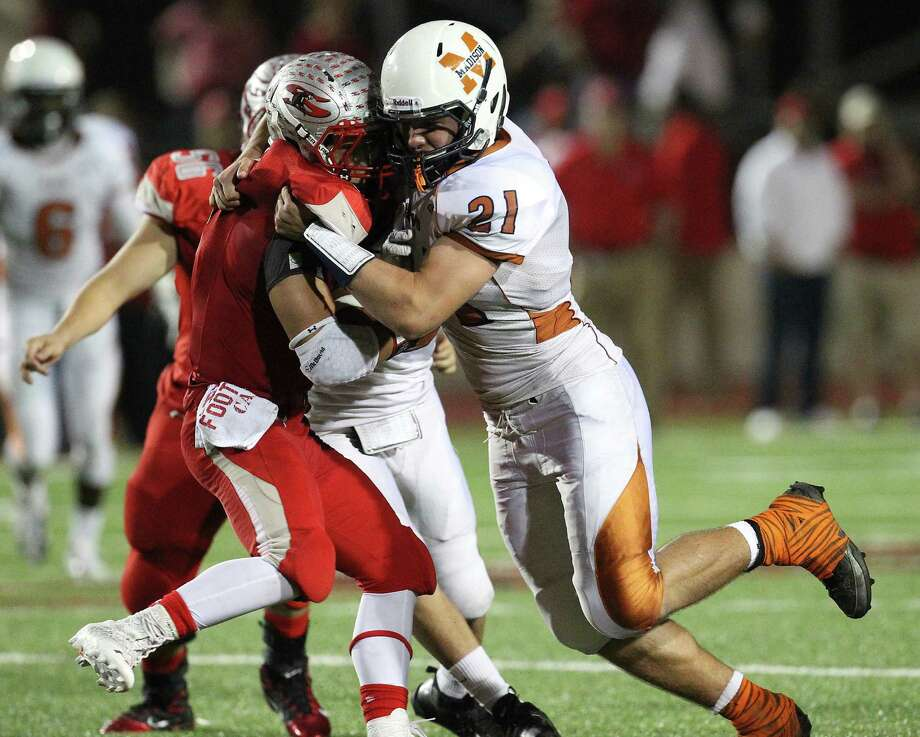 Madison's Daniel Yancey (21) makes a tackle on Mission Sharyland's Cesar Valdez (08) in the second half in the Class 5A Div. I playoff game in Corpus Christi on Friday, Nov. 30, 2012. Photo: Kin Man Hui, Express-News / © 2012 San Antonio Express-News