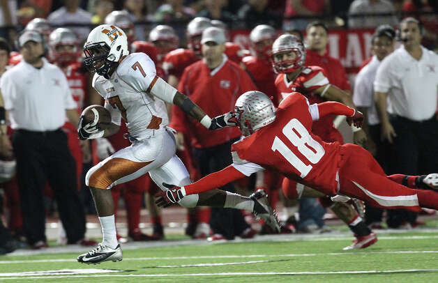 Madison's Marquis Warford (07) brushes off Mission Sharyland's Jon Barraza (18) on his way to a second half 75-yard touchdown in the Class 5A Div. I playoff game in Corpus Christi on Friday, Nov. 30, 2012. Photo: Kin Man Hui, Express-News / © 2012 San Antonio Express-News