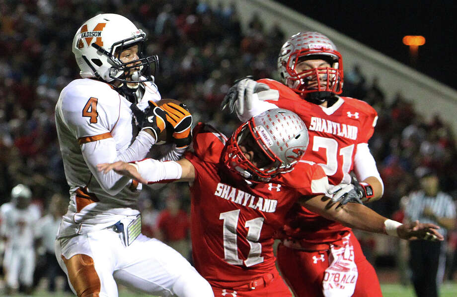Madison's Byron Daniels (04) makes a catch against Mission Sharyland's J.C. Valadez (11) and Sean Landez (21) and runs in for a touchdown in the first half in the Class 5A Div. I playoff game in Corpus Christi on Friday, Nov. 30, 2012. Photo: Kin Man Hui, Express-News / © 2012 San Antonio Express-News