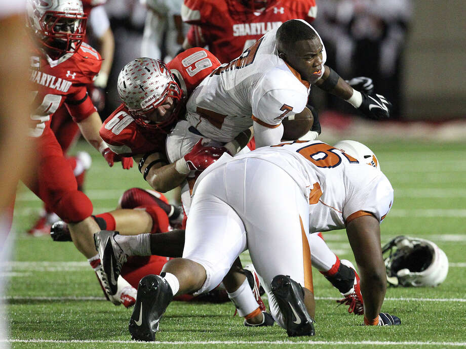 Madison's Marquis Warford (07) gets his helmet knocked off as Mission Sharyland's Marco Villarreal (60) goes for the tackle in the first half in the Class 5A Div. I playoff game in Corpus Christi on Friday, Nov. 30, 2012. Photo: Kin Man Hui, Express-News / © 2012 San Antonio Express-News