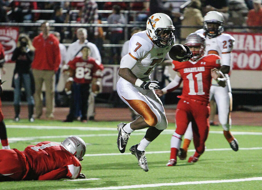Madison's Marquis Warford (07) hops into the end zone for a touchdown against Mission Sharyland's Francisco Campos (01) in the first half in the Class 5A Div. I playoff game in Corpus Christi on Friday, Nov. 30, 2012. Photo: Kin Man Hui, Express-News / © 2012 San Antonio Express-News