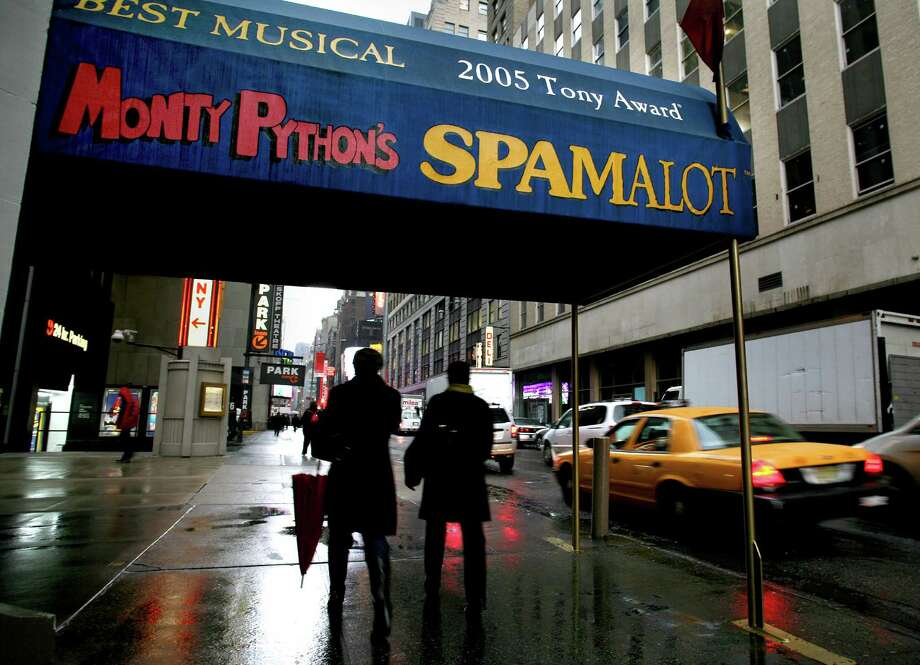 "FILE - In this Tuesday, Nov. 25, 2008 file photo, pedestrians walk under the marquee of the Broadway show ""Monty Python's Spamalot"" at the Shubert Theatre in New York. A producer of the film ""Monty Python and the Holy Grail"" is suing the comedy troupe over royalties from the hit stage musical ""Spamalot."" Producer Mark Forstater wants a bigger share of proceeds from the show, which is based on the 1975 movie spoof of the legend of King Arthur. Python members Eric Idle, Michael Palin and Terry Jones are to give evidence during a five-day hearing that began Friday, Nov. 30, 2012 at London's High Court. (AP Photo/Craig Ruttle, File ) Photo: Craig Ruttle"