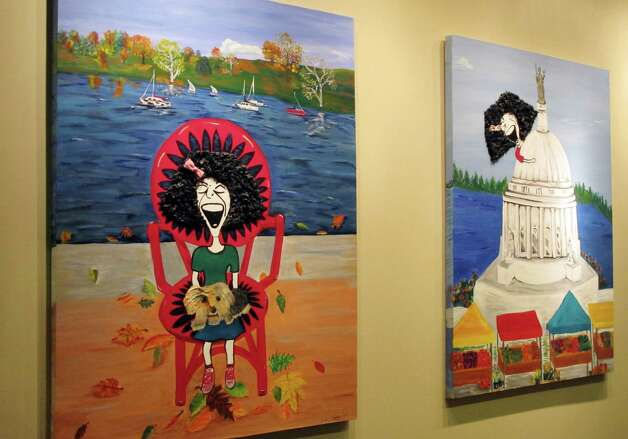 Paintings imagining comedian Gilda Radner in recognizable locations in Madison hang on the wall inside the cancer support group Gilda's Club Madison on Wednesday, Nov. 27, 2012, in Middleton, Wis. The Madison-area chapter of the national group is the latest to change its name to the Cancer Support Community, a move its director said was necessary because young people don't know who Radner was. (AP Photo/Scott Bauer) Photo: Scott Bauer